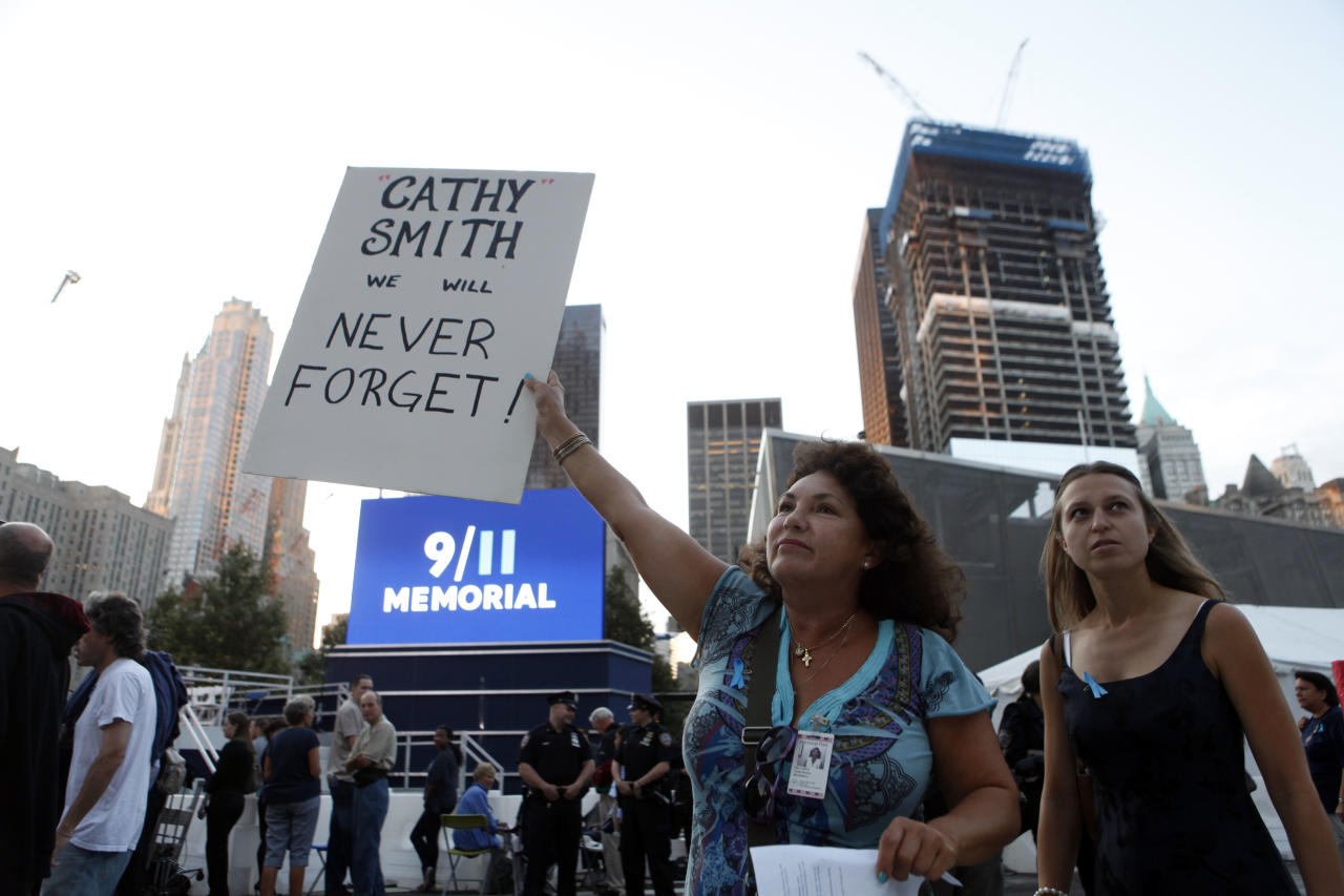Elba Cedeno, of Waretown, N.J., holds a sign memorializing her partner, Catherine Theresa Smith, as friends and relatives of the victims of 9/11 gather for a ceremony marking the 10th anniversary of the attacks at the National September 11 Memorial at the World Trade Center site, Sunday, Sept. 11, 2011, in New York. (AP Photo/Jason DeCrow)