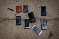 Wet phones and other items are placed on the ground by police officers as they inspect a boat where 15 Malians were found dead adrift in the Atlantic on Thursday, Aug. 20, 2020 in Gran Canaria island, Spain. The 15 lifeless men were spotted inside a boat on August 19 by a Spanish plane 80 nautical miles (148 kilometers, 92 miles) from the island of Gran Canaria. Police collected what was left behind as evidence: a wallet, a dozen cell phones, windbreakers and waterproof boots. (AP Photo/Emilio Morenatti)