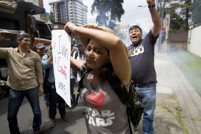 Supporters of Commissioner Ivan Velasquez, front, holds a sing as anti-CICIG protestor, back, fires fireworks in front of the United Nations International Commission Against Impunity, CICIG, headquarters in Guatemala City, Friday, Aug. 31, 2018. Guatemala president Jimmy Morales says he is not renewing mandate of U.N.-sponsored commission investigating corruption in the country. (AP Photo/Moises Castillo)