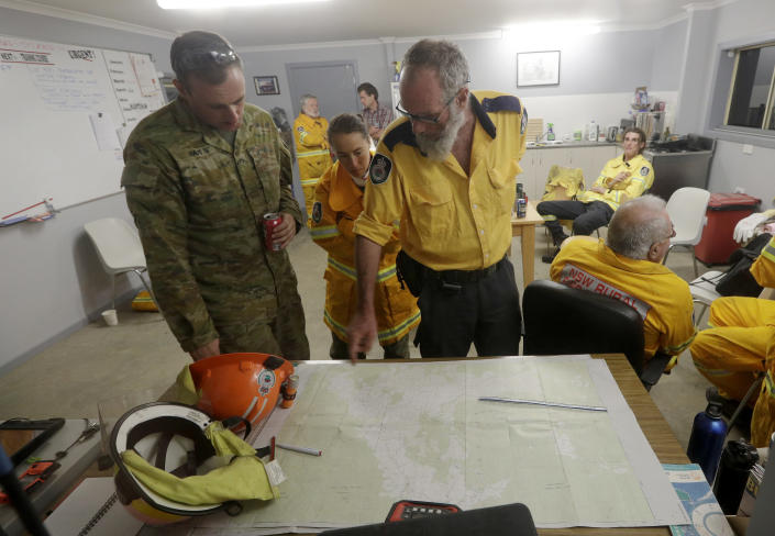 Firefighters and members of the army discuss a nearby fire threat at the Burragate, Australia, firehouse, Friday, Jan. 10, 2020. Thousands of people are fleeing their homes and helicopters are dropping supplies to towns at risk of wildfires as hot, windy conditions threaten already fire-ravaged southeastern Australian communities. The danger is centered on Australia's most populous states, including coastal towns that lost homes in earlier fires. (AP Photo/Rick Rycroft)