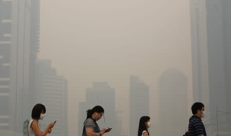 File photo of office workers wearing masks making their way to work in Singapore's central business district