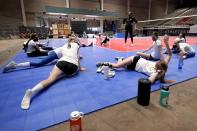 Setter Samantha Seliger-Swenson (3) looks over as a teammate directs a question to coach Tayyiba Haneef-Park, center rear, after an afternoon volleyball practice in Dallas, Wednesday, Feb. 24, 2021. (AP Photo/Tony Gutierrez)