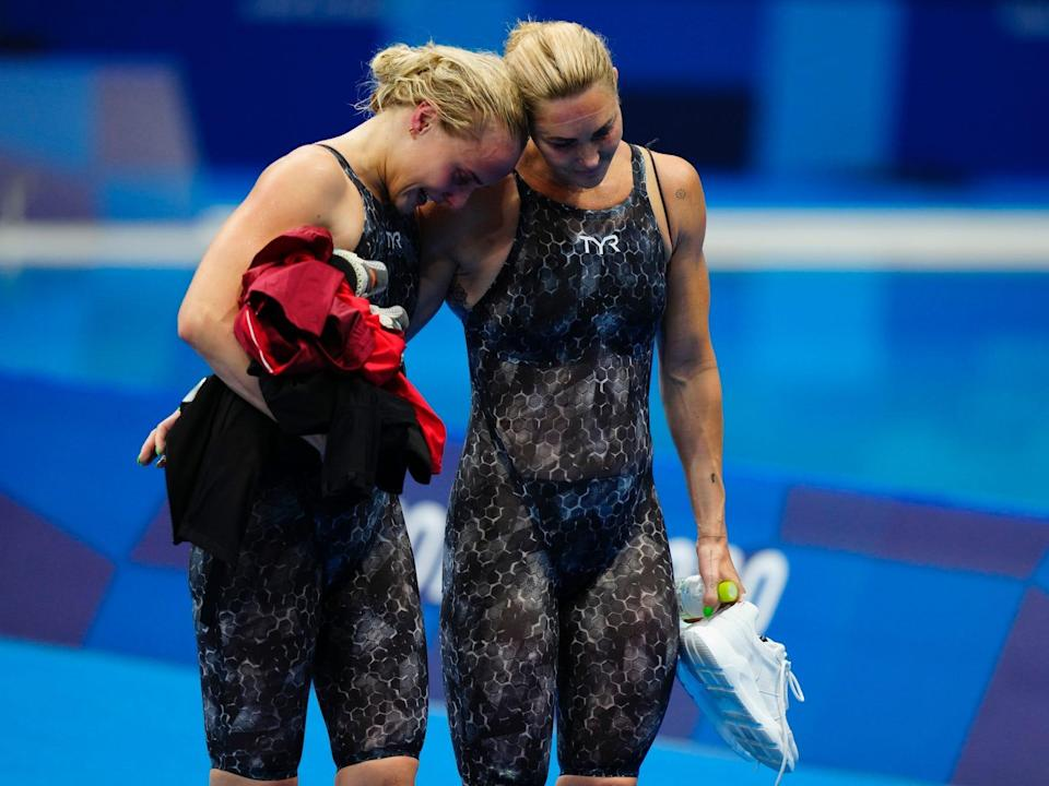 Two Danish swimmers comfort each other at the Tokyo Olympics.