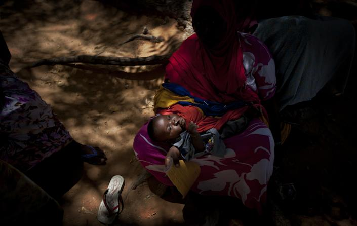 A Somali mother and her baby wait in partial shade in a courtyard after her baby received a five-in-one vaccine against several potentially fatal childhood diseases, at the Medina Maternal Child Health center in Mogadishu, Somalia Wednesday, April 24, 2013. On the eve of the Global Vaccine Summit in Abu Dhabi and coinciding with World Immunization Week, the authorities in Somalia, which has one of the lowest immunization rates in the world, launched the new deployment of a pentavalent vaccine against diphtheria, tetanus, whooping cough, hepatitis B, and haemophilus influenzae type B the bacteria that causes meningitis and pneumonia. (AP Photo/Ben Curtis)