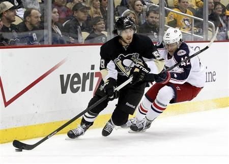 Dec 9, 2013; Pittsburgh, PA, USA; Pittsburgh Penguins defenseman Kris Letang (58) handles the puck against pressure from Columbus Blue Jackets center Artem Anisimov (42) during the third period at the CONSOL Energy Center. The Penguins won 2-1. Mandatory Credit: Charles LeClaire-USA TODAY Sports