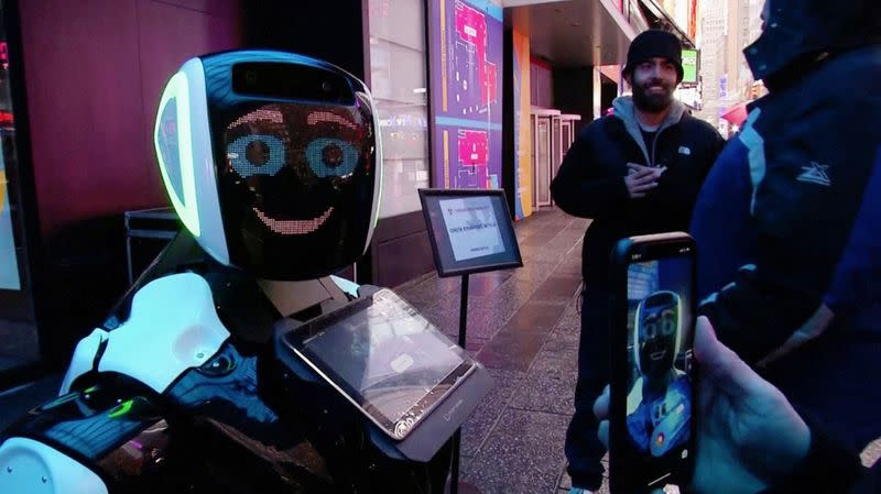 Passers-by in Times Square interact with a Promobot robot that informs the public about the symptoms of coronavirus and how to prevent it from spreading, in this still frame obtained from video, in New York City