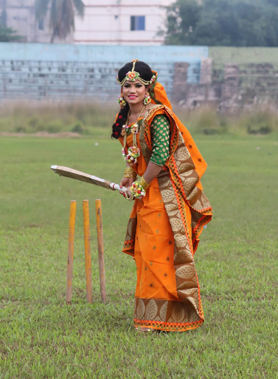 Bangladeshi cricketer Sanjida Islam poses as a bride with a cricket bat, a day before her wedding day in Rangpur, Bangladesh, Friday, Oct. 16. (Sobhana Mostary via AP)