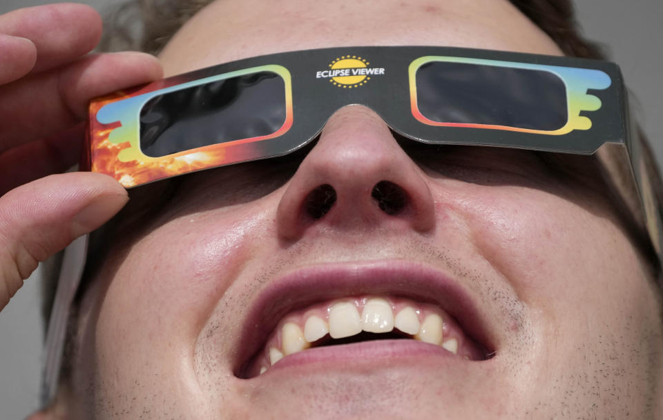 A man wears special glasses to watch the partial solar eclipse in Trafalgar Square in London, Thursday, June 10, 2021. (AP Photo/Frank Augstein)