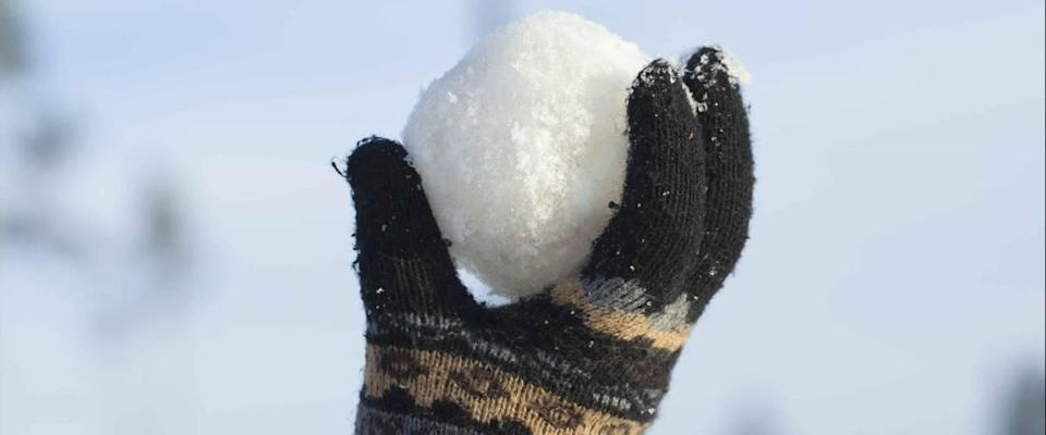 Snowball in hand on blue sky background