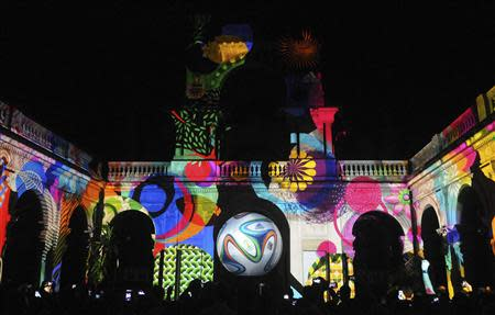"""People take pictures of the official match ball for the 2014 World Cup named """"brazuca"""" which is projected on a building at Lage Park during a presentation ceremony in Rio de Janeiro in this December 3, 2013 file photo. REUTERS/Stringer/Files"""