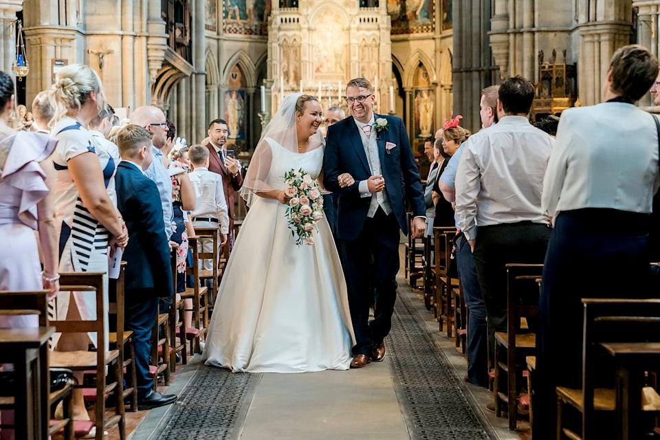 The couple made their way back down the aisle after saying 'I do' [Photo: SWNS]