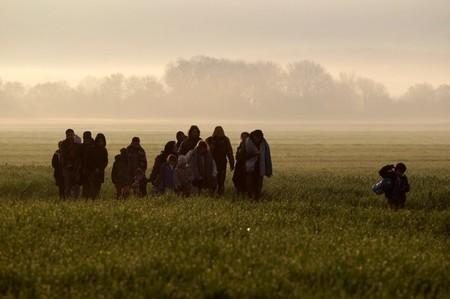 Refugees and migrants walk towards a makeshift camp near the village of Idomeni