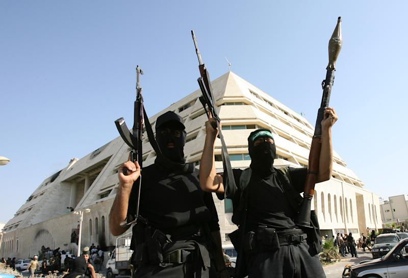 Hamas fighters tot their arms as they stand in front of the pro-Fatah Palestinian Intelligence Security compound in Gaza City, 14 June 2007 (AFP Photo/Mahmud Hams)