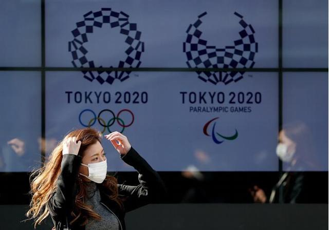 A passerby wearing a protective face mask following an outbreak of the coronavirus disease (COVID-19) walks past a screen displaying logos of Tokyo 2020 Olympic and Paralympic Games in Tokyo