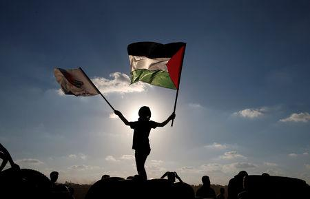 A boy waves a Palestinian flag during a protest calling for lifting the Israeli blockade on Gaza and demanding the right to return to their homeland, at the Israel-Gaza border fence, east of Gaza City September 14, 2018. REUTERS/Mohammed Salem