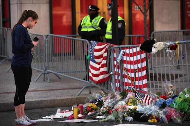 BOSTON, MA - APRIL 17: A woman looks at a street memorial near the scene of twin bombings at the Boston Marathon on April 17, 2013 in Boston, Massachusetts. The explosions, which occurred near the finish line of the 116-year-old Boston race on April 15, resulted in the deaths of three people with more than 170 others injured. Security has been heightened across the nation as the search continues for the person or people behind the bombings. (Photo by Spencer Platt/Getty Images)