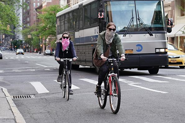 People ride bikes while wearing face coverings during the coronavirus pandemic in New York City.