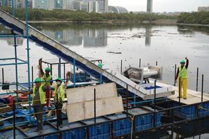 Workers celebrate completing the installation of RiverRecycle's collector on the banks of Mithi River in Mumbai. The system aims to collect between 70 and 200 tons of river waste daily.