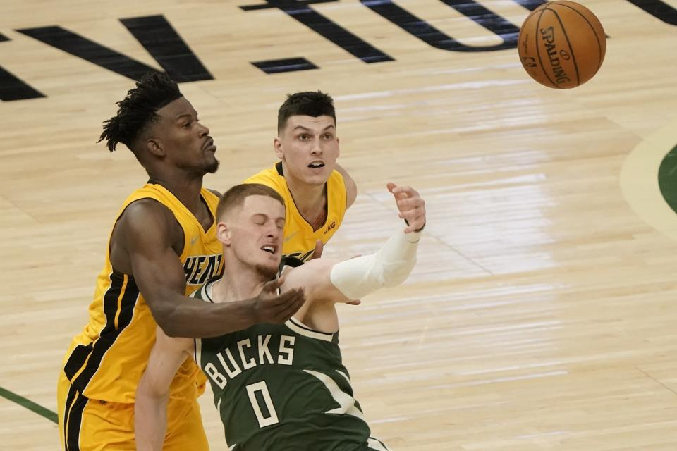 Milwaukee Bucks' Donte DiVincenzo goes after a loose ball with Miami Heat's Tyler Herro and Jimmy Butler during the second half of Game 1 of their NBA basketball first-round playoff series Saturday, May 22, 2021, in Milwaukee. (AP Photo/Morry Gash)