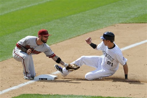 In this photo provided by the Colorado Rockies, Colorado Rockies' Tyler Colvin, right, is tagged out by Arizona Diamondbacks third baseman Ryan Roberts while attempting to steal third base in the second inning of a baseball game in Denver on Thursday, May 17, 2012. The Diamondbacks won 9-7. (AP Photo/Colorado Rockies, Ryan McKee, Rich Clarkson and Associates LLC)