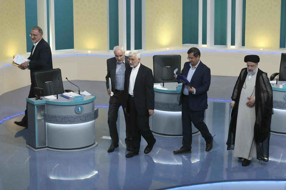 """In this picture made available by Young Journalists Club, YJC, presidential candidates for June 18, elections Alireza Zakani, left, Mohsen Mehralizadeh, second left, Saeed Jalili, center, Abdolnasser Hemmati, second right, and Ebrahim Raisi leave at the conclusion of a part of the final debate of the candidates at a state-run TV studio in Tehran, Iran, Saturday, June 12, 2021. Iran's seven presidential candidates offered starkly different views Saturday in the country's final debate, with hard-liners describing those seeking ties with the West as """"infiltrators"""" and the race's sole moderate warning a hard-line government would only bring more sanctions for the Islamic Republic. (Morteza Fakhri Nezhad/ Young Journalists Club, YJC via AP)"""