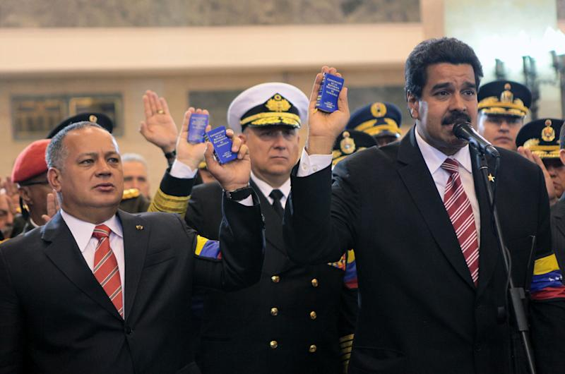 In this photo released by Miraflores Press Office, Venezuela's acting President Nicolas Maduro, right, the President of the National Assembly Disdado Cabello, left, and Defense Minister Adm. Diego Molero, center, hold up miniature copies of Venezuela's Constitution during a symbolic swearing in ceremony for Maduro in front of Venezuela's late President Hugo Chavez's coffin at the military academy where the funeral ceremony was held earlier, in Caracas, Venezuela, Friday, March 8, 2013. Chavez died on March 5 after a nearly two-year bout with cancer. Maduro was sworn in at the National Assembly earlier against the objections of the political opposition who said the move violated the country's constitution.  (AP Photo/Miraflores Press Office)