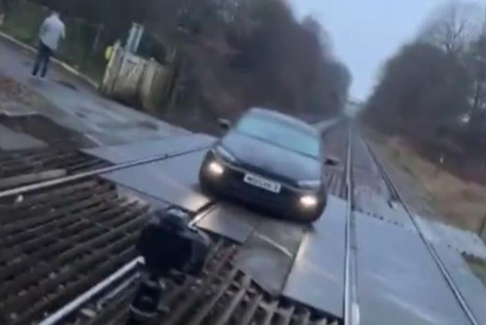 <p>A still from the video of a car parked at a level crossing in Bolton</p> (TikTok)