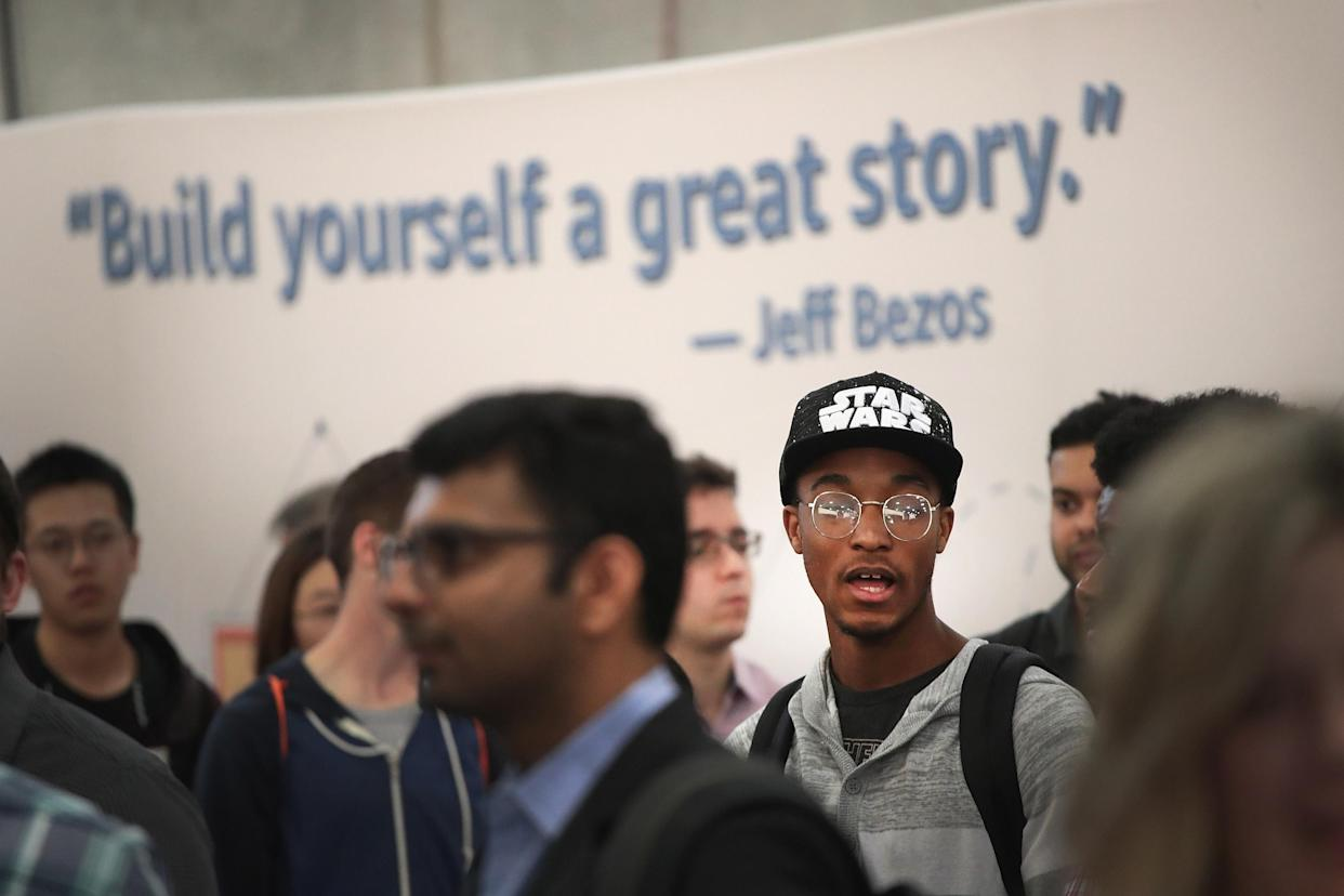 Job seekers wait in line to speak with Amazon recruiters and other company volunteers about job opportunities at Amazon during a career fair held at Vertiport Chicago on September 17, 2019 in Chicago, Illinois. (Photo by Scott Olson/Getty Images)
