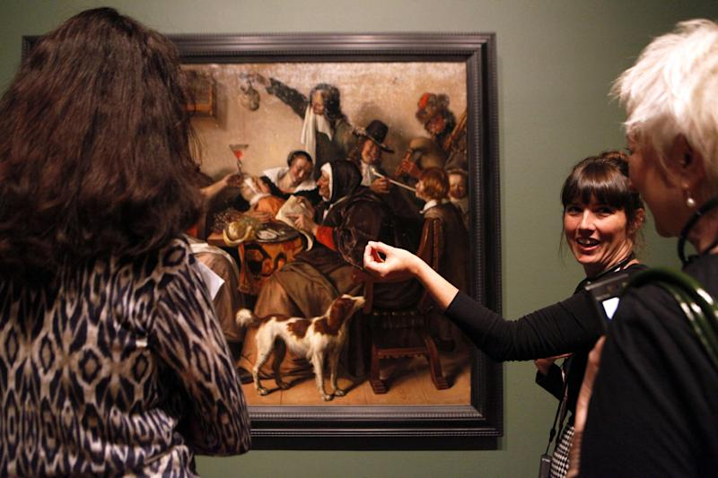 """This June 19, 2013 photo shows Nicole Cromartie, coordinator of museum interpretation at the High Museum of Art, speaking with visitors about Jan Steen's painting """"As the Old Sing, So Twitter the Young"""" on display in the """"Girl with a Pearl Earring: Dutch Paintings from the Mauritshuis"""" exhibit during a media preview at the museum in Atlanta. The exhibit, which opens Sunday and runs through Sept. 29, includes Johannes Vermeer's famous """"Girl With a Pearl Earring"""" painting and 34 other works from the Dutch Golden Age. (AP Photo/Jaime Henry-White)"""