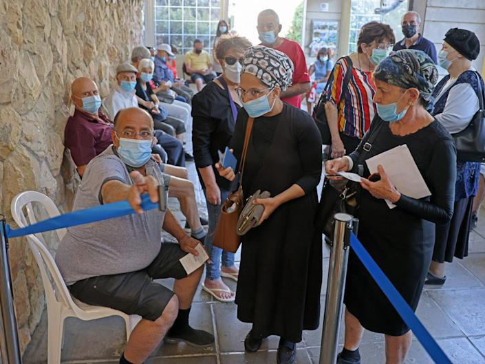 Israelis arrive to get their third dose of the Pfizer-BioNtech COVID-19 vaccine at the Clalit Health Service in Jerusalem on August 1, 2021, as Israel launches its campaign to give booster shots to people aged over 60.