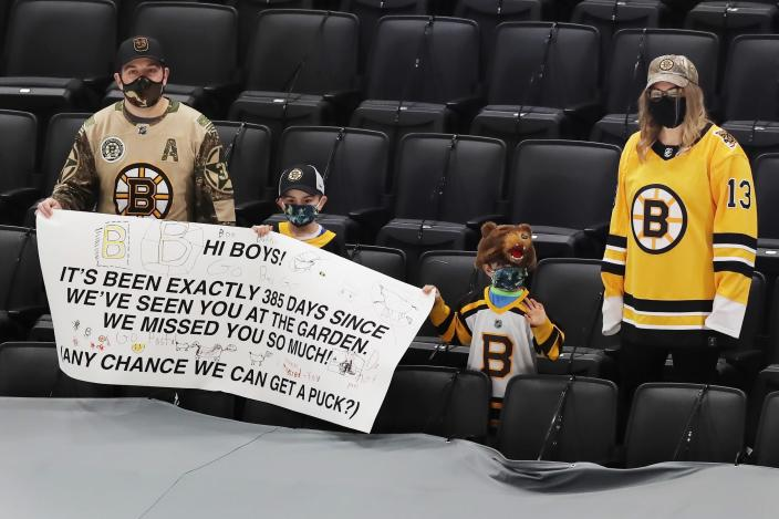 Fans watch warm-ups before an NHL hockey game between the Boston Bruins and the Buffalo Sabres, Saturday, March 27, 2021, in Boston. (AP Photo/Michael Dwyer)