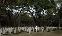 "FILE - In this Sunday, Nov. 13, 2016 file photo, a Kenyan naval officer pauses as he walks amongst the graves before observing Remembrance Sunday, to honor the contribution of those British and Commonwealth military who died in the two World Wars and later conflicts, at the Nairobi War Cemetery in Kenya. The Commonwealth War Graves Commission has apologized after an investigation found that at least 161,000 mostly Africans and Indians who died fighting for the British Empire during World War I weren't properly honored due to ""pervasive racism"", according to findings released Thursday, April 22, 2021. (AP Photo/Ben Curtis, File)"