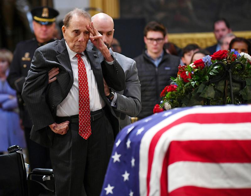 "Bob Dole saluted a fellow World War II veteran under the Capitol dome as he rose to honor George H.W. Bush on Dec. 4, 2018. Dole, the 95-year-old former Senate majority leader, relied on an aide to help him stand on the floor of the Capitol rotunda before offering his gesture beside the casket of Bush, his onetime rival in the 1988 Republican presidential primary. Bush's spokesman, Jim McGrath, described the salute as ""a last, powerful gesture of respect from one member of the Greatest Generation, @SenatorDole, to another.""Dole was among mourners filing into the rotunda to pay respects to Bush on day two of his lying in state, a day that also drew Colin Powell, his former Joint Chiefs of Staff chairman, and Sully, the yellow Labrador who worked as the former president's service dog."