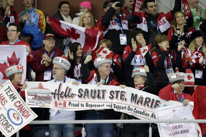 Supporters of Canada's curling team celebrate after they beat Germany during the men's curling competition at the 2014 Winter Olympics, Monday, Feb. 10, 2014, in Sochi, Russia. (AP Photo/Wong Maye-E)