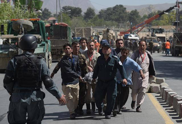 <p>Afghan volunteers carry victims at the site of a car bomb attack in Kabul on May 31, 2017. (Shah Marai/AFP/Getty Images) </p>