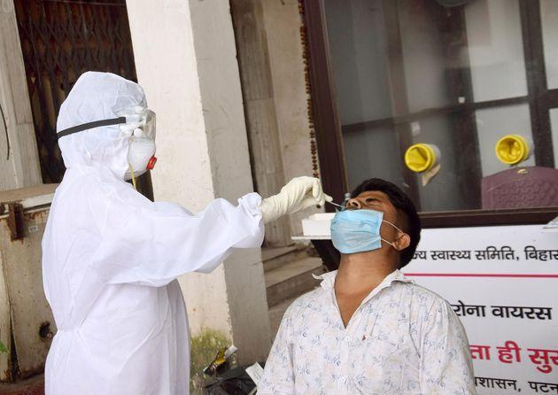 A health worker collects a swab sample from a man for coronavirus testing, at Gardiner Hospital, on August 26, 2020 in Patna.
