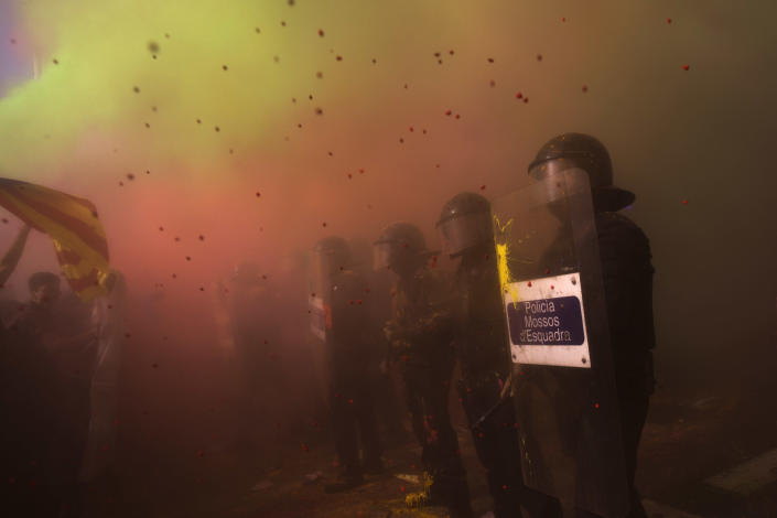 Demonstrators throw powdered paint at Catalan police officers during clashes with pro independence protesters on their way to meet demonstrations of members and supporters of National Police and Guardia Civil in Barcelona on Saturday, Sept. 29, 2018. (AP Photo/Emilio Morenatti)
