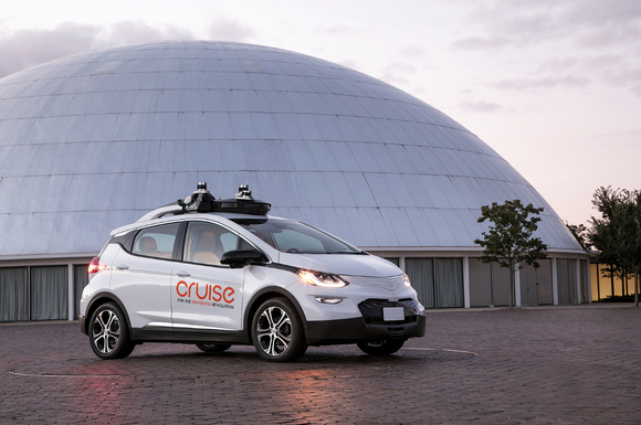 A white Chevrolet Bolt EV with Cruise Automation logos and visible self-driving hardware parked outside of the Design Dome at GM's historic Technical Center in Warren, Michigan.