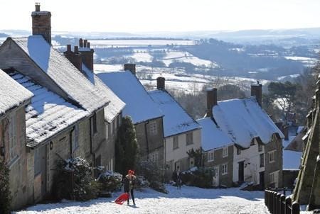 FILE PHOTO: People toboggan in the snow on Gold Hill in Shaftesbury, southwest Britain
