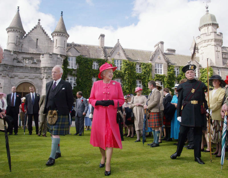 The final day of the Golden Jubilee tour ends with a Garden Party in the grounds of the Queen's home at Balmoral Castle. Queen Elizabeth II walks through the gardens to meet some of her 3,000 guests. On her right, dressed in traditional uniform with a distinctive feathered cap, is a member of the Royal Company of Archers, who act as the Queen's official bodyguards when she is in Scotland. (Photo by © Pool Photograph/Corbis/Corbis via Getty Images)