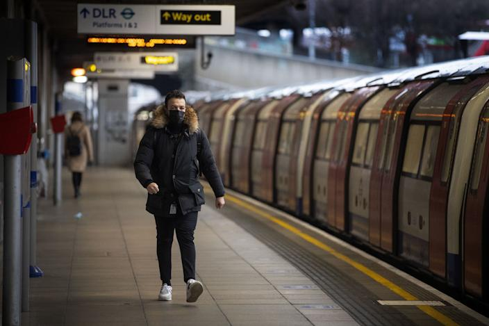 Commuters getting on a Jubilee Line Underground train at Canning Town station during the morning rush hour in London, as England's third national lockdown to curb the spread of coronavirus continues.