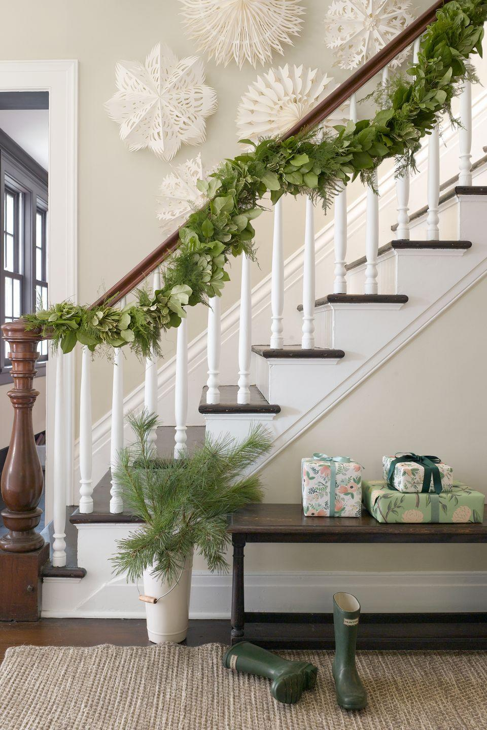 """<p>A handmade garland and giant paper snowflakes welcome guests with the holiday spirit. If you'd like, get creative with interesting details like feathers or pinecones tied with a gingham bow to the garland.</p><p><a class=""""link rapid-noclick-resp"""" href=""""https://www.amazon.com/s/ref=nb_sb_noss?url=search-alias%3Dgarden&field-keywords=christmas+garland&tag=syn-yahoo-20&ascsubtag=%5Bartid%7C10050.g.1247%5Bsrc%7Cyahoo-us"""" rel=""""nofollow noopener"""" target=""""_blank"""" data-ylk=""""slk:SHOP GARLAND"""">SHOP GARLAND</a><br></p>"""