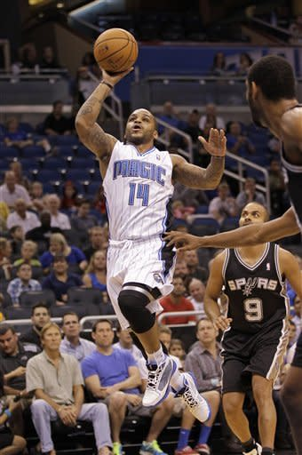 Orlando Magic's Jameer Nelson (14) goes up for a shot past San Antonio Spurs' Tony Parker (9), of France, and power forward Tim Duncan, right, during the first half of an NBA preseason basketball game, Sunday,Oct. 21, 2012, in Orlando, Fla. (AP Photo/John Raoux)