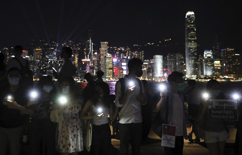 Demonstrators hold their smartphones as they gather at the Tsim Sha Tsui waterfront in Hong Kong, Friday, Aug. 23, 2019. Supporters of Hong Kong's pro-democracy movement created human chains on both sides of the city's harbor Friday, inspired by a historic protest 30 years ago in the Baltic states against Soviet control. (AP Photo/Vincent Yu)