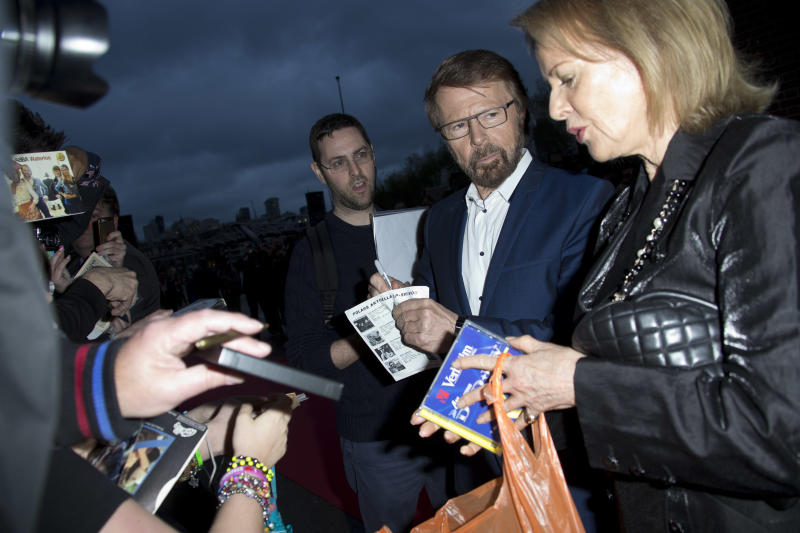 Swedish singer's Bjorn Ulvaeus, 2nd right, and Anni-Frid Lyngstad, right, of the pop group ABBA, sign autographs as they arrive on the red carpet for the band's International anniversary party at the Tate Modern in central London, Monday, April 7, 2014. The event marks the launch of ABBA – The Official Photo Book, the first ever authorised photographic biography of the band. (Photo by Joel Ryan/Invision/AP Images)
