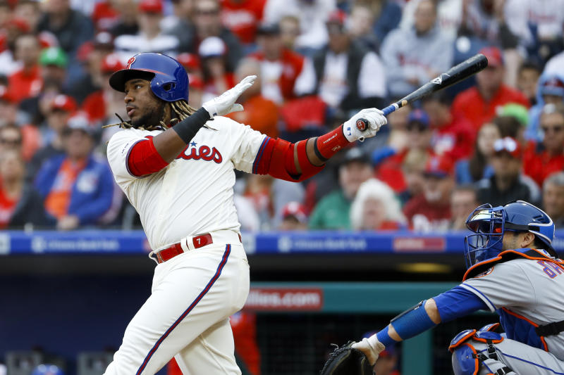 Philadelphia Phillies' Maikel Franco, left, follows through after hitting an RBI-sacrifice fly off New York Mets starting pitcher Zack Wheeler during the second inning of a baseball game, Wednesday, April 17, 2019, in Philadelphia. At right is Mets catcher Travis d'Arnaud. (AP Photo/Matt Slocum)
