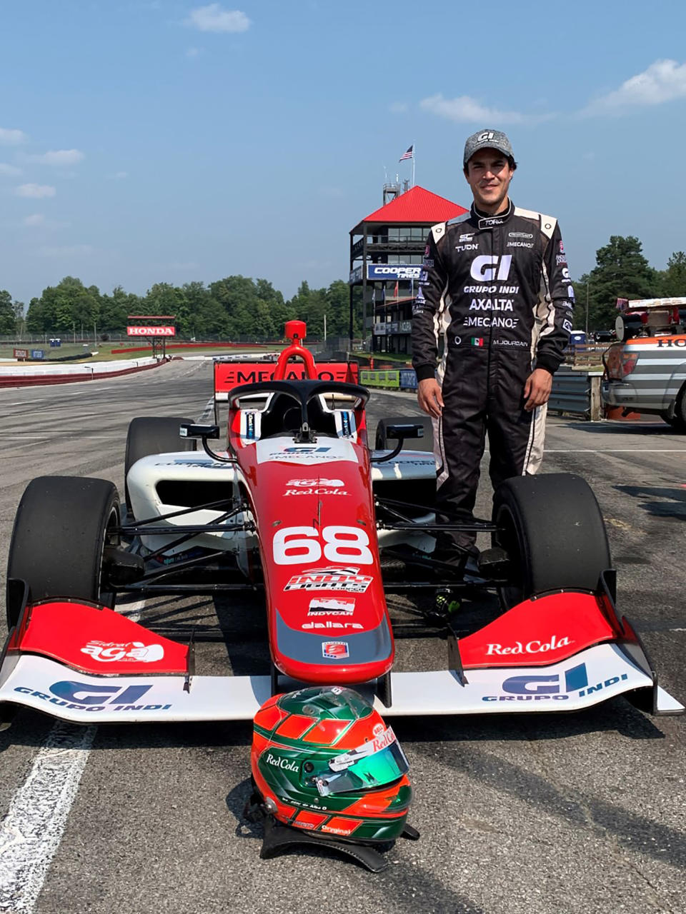 Salvador de Alba Jr., of Guadalajara, poses beside the Indy Lights car he will test at the Mid-Ohio Sports Car Course in Lexington, Ohio, on Saturday, July 3, 2021. Just driving the Lights car for Andretti would have been enough to call his trip to Ohio a success. But de Alba had a fully immersive experience that went beyond his wildest dreams. (AP Photo/Jenna Fryer)