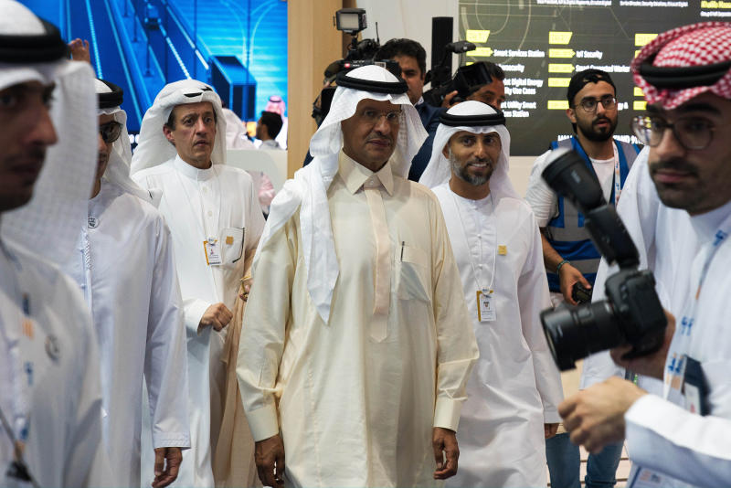 Saudi Arabia's new Energy Minister Prince Abdulaziz bin Salman, center, and United Arab Emirates Energy Minister Suhail al-Mazrouei, right, walk through an energy exhibition in Abu Dhabi, United Arab Emirates, Monday, Sept. 9, 2019. Prince Abdulaziz, as well as the CEOs of Total SA and ENI SpA, were in Abu Dhabi on Monday at the World Energy Congress. (AP Photo/Jon Gambrell)