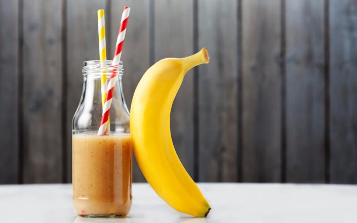 Glass bottle of banana smoothie and a banana - Westend61