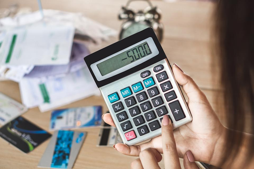 woman hand holding calculator showing number budget deficit for credit card debt payment with some bills on desk